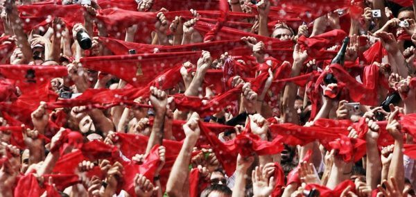 Revellers hold up traditional red scarves during the start of the San Fermin festival in Pamplona