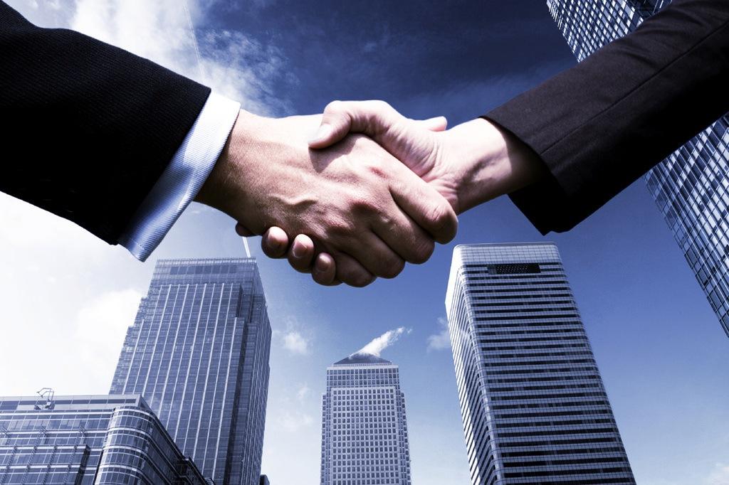 Plan-Compromiso-Empresa-Ventajas-manos-estrechadas-frente-edificios